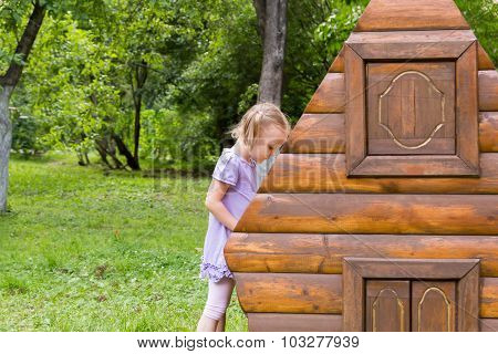 Little Girl With Pigtails Playing In Toy Log Cabin
