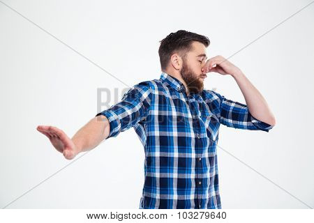 Portrait of a casual man covering his nose and showing stop gesture with palm isolated on a white background