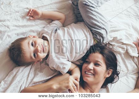 Young mother with her 2 years old son dressed in pajamas are relaxing and playing in the bed at the weekend together, lazy morning, warm and cozy scene. Pastel colors, selective focus, top view.