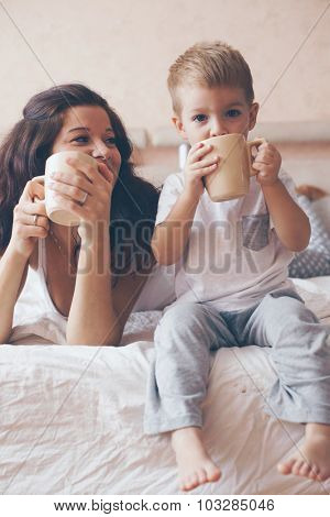 Young mother with her 2 years old little son dressed in pajamas are relaxing and playing in the bed at the weekend together, lazy morning, warm and cozy scene. Pastel colors, selective focus.