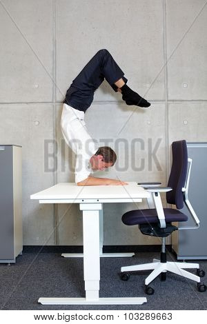 flexible business man in scorpion asana on desk in his office - profile view