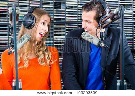 Presenters or moderators - man and woman - in radio station hosting show for radio live in Studio