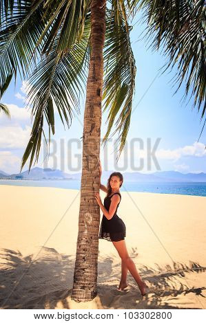 Slim Girl In Black Lace Frock Barefoot Touches Palm On Beach