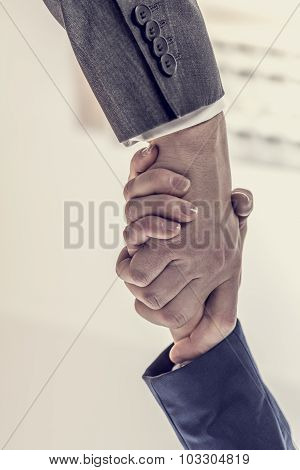 Retro image of business partners - man and woman shaking hands to close a deal in agreement greeting or congratulations view from underneath their hands. poster