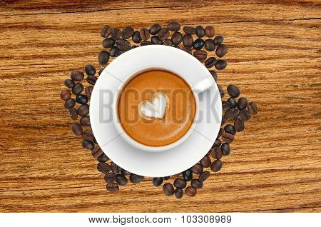 Latte Coffee With Heart Symbol Over Roasted Coffee Beans On Wooden Table