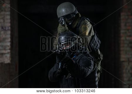 Fully equipped military men with automatic weapons playing airsoft strikeball
