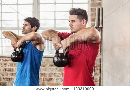 Muscular men lifting a kettle bell in crossfit gym