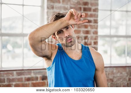 Man wiping his forehead with arm at the gym poster