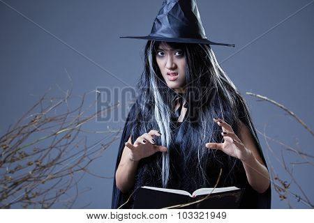 young witch casting a spell and holding a book poster