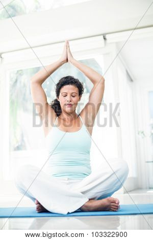 Full length of pregnant woman performing yoga on exercise mat with hands joined at home