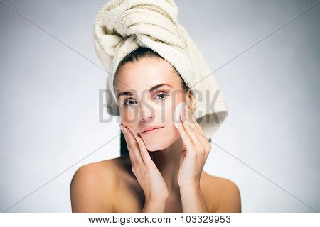 Healthy fresh girl cleaning face with cotton swab poster