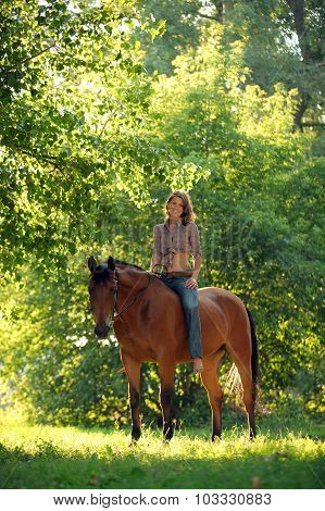 Cowgirl ride horse in summer evening woods
