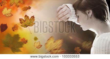 Sad pretty brunette leaning against wall against autumn scene