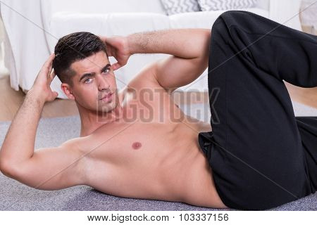 Sporty man doing oblique crunches on the floor poster