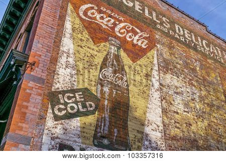 FORT COLLINS, CO, USA, AUGUST 30,  2015: A vintage ad for Coca-Cola - a faded mural on a building wall in Fort Collins old town.