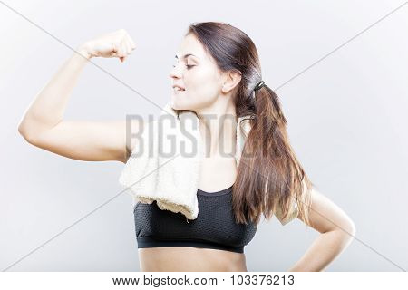 Smiling Woman Looking At Her Biceps After Exercise