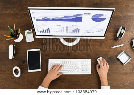 Businessperson Analyzing Statistical Graph On Computer