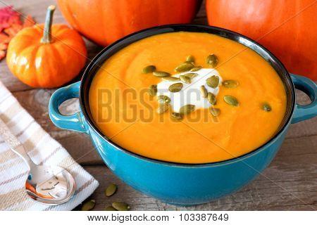 Creamy pumpkin soup in a blue bowl close up
