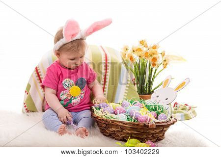 Baby girl with bunny ears and Easter basket with eggs