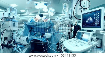 In advanced operating room with lots of equipment patient and working surgical specialists poster