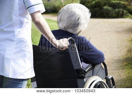 Close Up Of Carer Pushing Senior Woman In Wheelchair