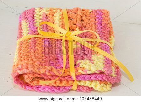 Handmade crocheted dishcloths made with different stitches and multicolored yarn.
