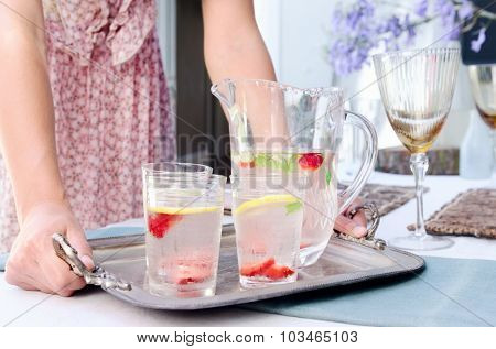 Party hostess carries a tray of drinks to the table in a domestic garden environment, fresh cut fruit in ice water