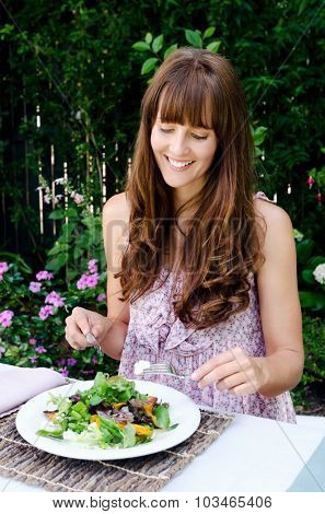 Woman eating a healthy salad lunch in a outdoor garden cafe alfresco style