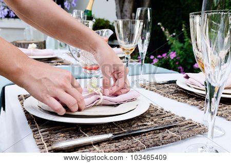 Pair of hands making final adjustments to a napkin for a simple rustic country style table setting, a party gathering in a casual outdoor garden setting