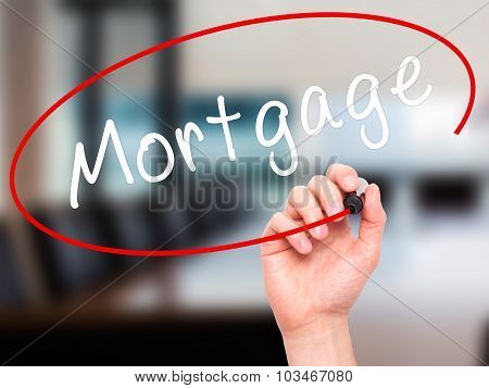 Man Hand writing Mortgage with black marker on visual screen.