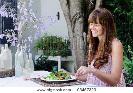 Pretty woman eating healthy green salad outdoors in garden, relaxed and happy in alfresco dining