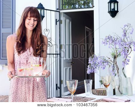 Party hostess carries a tray of drinks to the table in a domestic garden environment