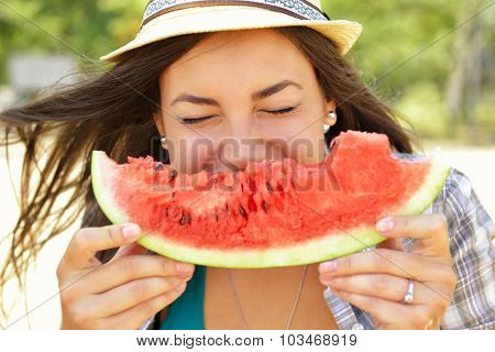 Happy young woman eating watermelon on the beach. Youth lifestyle. Happiness, joy, holiday, beach, summer concept.