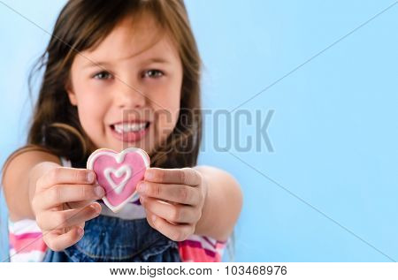 Happy smiling adorable young girl in denim dungarees holds out a pink heart shape cookie, selective focus on cookie, valentines or mothers day concept