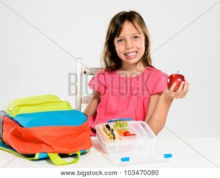 Happy smiling school girl holds red apple over her healthy lunchbox filled with fresh fruit and sandwich