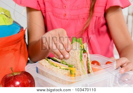 Close up on pair of young girl's hands removing a healthy wholesome wholemeal bread ham sandwich from her lunch box during lunch period