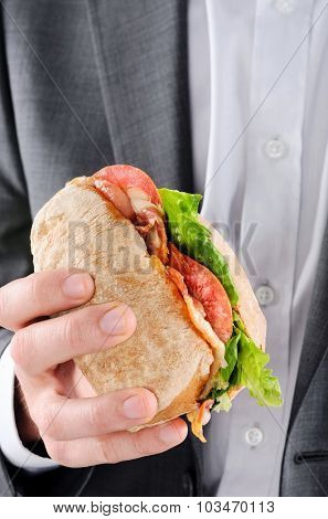 Businessman holding to a BLT sandwich, busy lunch on the go, hands only