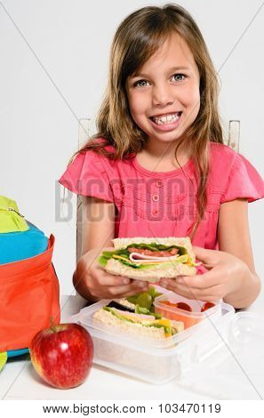Cute young girl smiles and holds her healthy wholemeal sandwich over her lunch box and school backpack