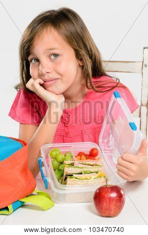 Happy smiling school girl opens her healthy lunchbox filled with fresh fruit and sandwich