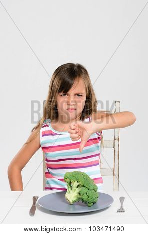 Cute young child kid making disgusted disapproving face at her food, healthy eating food choice concept
