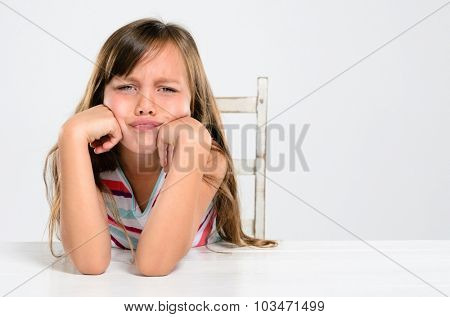 Portrait of young preschool girl pouting and throwing a tantrum at a table
