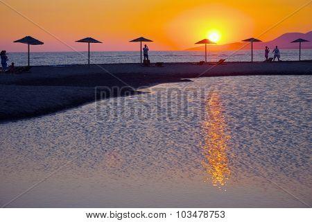 sunset on beach umbrella of Ada Bojana island, Montenegro poster