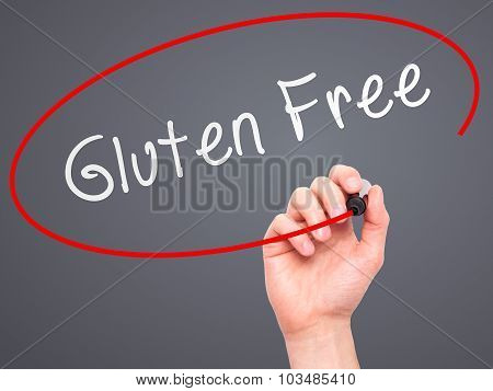 Man Hand writing Gluten Free with marker on transparent wipe board.