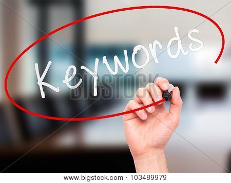 Man Hand writing Keyword with black marker on visual screen.