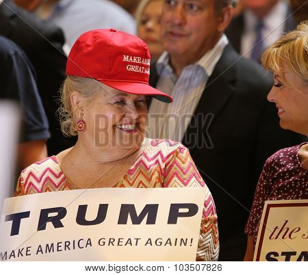 Trump supporter in red hat with sign
