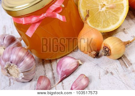Fresh organic honey in glass jar onion garlic and lemon on old wooden background healthy nutrition strengthening immunity and treatment of flu poster