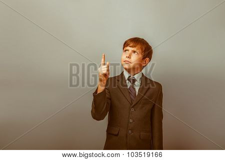 a boy of twelve European appearance in a suit shows his finger t
