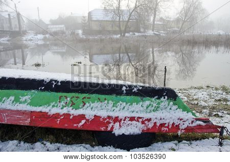 Upturned Boat By The River In Winter Time