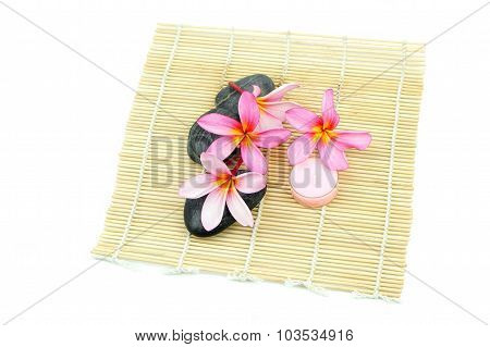 Tropical spa setting on bamboo mat on white background