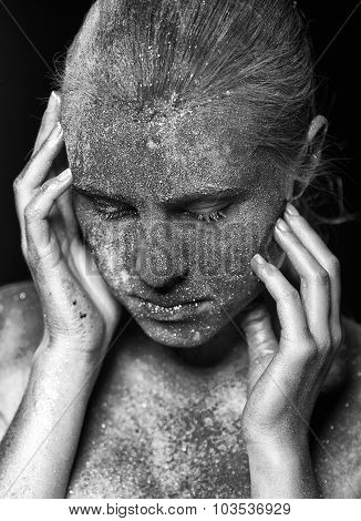 Young woman portrait. Girl in dust and dirt posing in studio with hands near by face